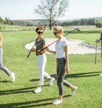 Young friends dressed casually walking with putters on the golf course during a game on a sunny day